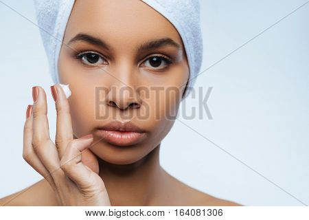 For shiny skin. Attractive pretty nice woman having some moisturizing cream on her finger and preparing to apply it while wearing towel turban