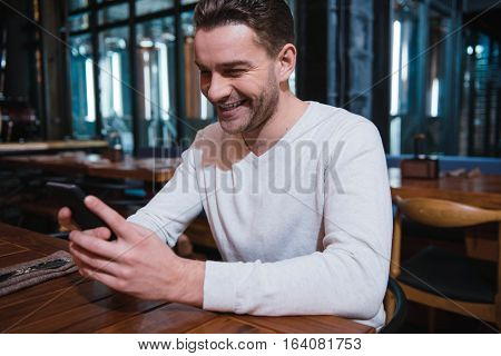 Electronic device. Happy nice pleasant man holding his smartphone and laughing while looking at its screen