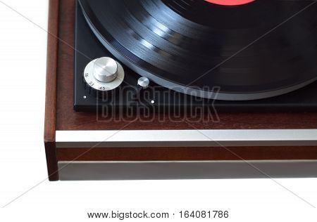 Part of vintage record player with wood finish with black LP vinyl record top view isolated on white horizontal photo closeup
