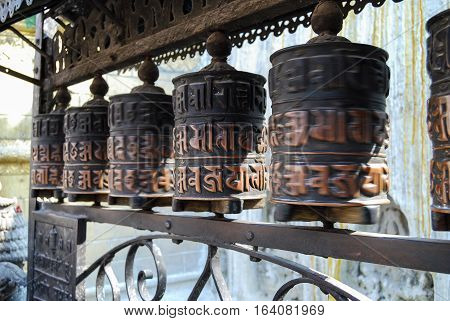 Spinning prayer wheels with mantra in buddha temple. Nepal