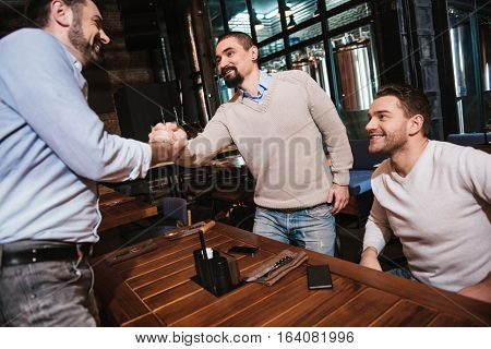 Long time no see. Pleasant bearded positive man standing opposite his friend and shaking his hand while greeting him