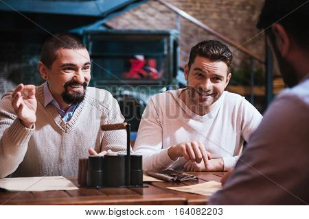 Involved in the conversation. Cheerful happy handsome men sitting at the table and looking at their friend while having a discussion