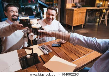 Pleasant company. Happy nice male friends sitting in the pub and enjoying their time together while meeting on Friday evening