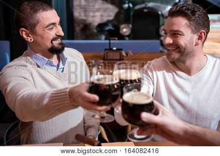 Drinking beer. Selective focus of nice cheerful handsome man holding glasses with beer and cheering with them while looking at each other