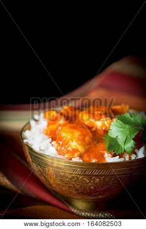 Indian butter chicken served on a bowl of basmati rice.