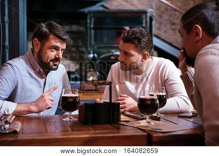 Pleasant interaction. Handsome bearded nice man sitting at the table and holding his finger up while telling something to his friends
