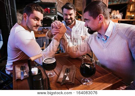 Who is stronger. Good looking strong male friends sitting opposite each other and arm wrestling while deciding who is stronger.