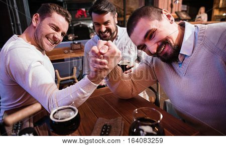 Cheerful pleasant strong men gathering their strength and trying to defeat each other while arm wrestling in the pub.