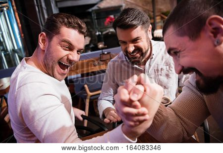 Nice handsome brutal man looking at his rival and gathering all his strength while trying to win the arm wrestling match