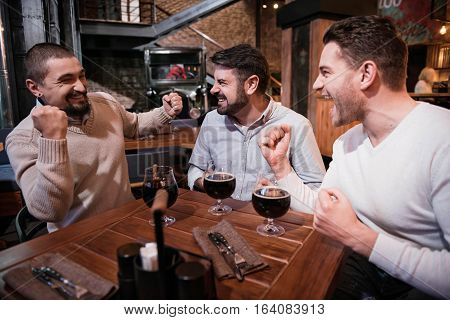 Absolutely happy. Positive delighted jubilant men sitting at the table and gesticulating while expressing their emotions
