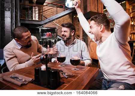 Wonderful emotions. Joyful positive nice man sitting with his friends at the table and holding his hands up while cheering with them
