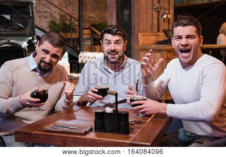 Tense game. Good looking emotional pleasant men enjoying their beer and watching sports games while meeting in the pub at the weekends