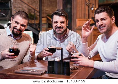 Watching TV. Positive joyful emotional men sitting at the table and supporting their football team while watching sports games in the pub