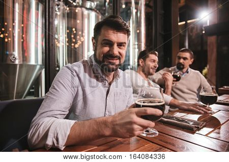 Time with friends. Cheerful nice positive man holding a glass with beer and putting in on the table while looking at you