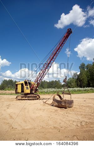 Yellow excavator with big heavy bucket standing on sand on background of forest and clear blue sky on a summer day vertical view