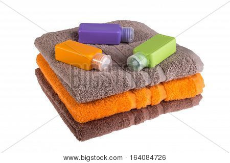 Colorful towels and small plastic bottles for travel on a white background