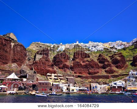 Oia town on red caldera cliff and marina down by the sea. Santorini Greece.