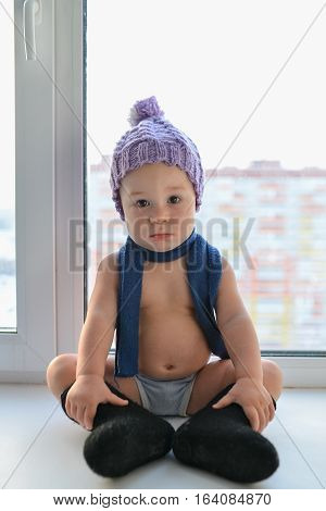 Adorable one year old baby boy lonely sitting on the windowsill weared in winter hat, shoes and scarf, at home.
