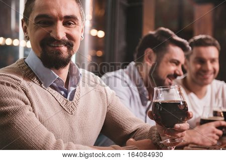 Lets drink for friendship. Pleasant joyful delighted man raising his glass with beer and smiling while drinking for his friends