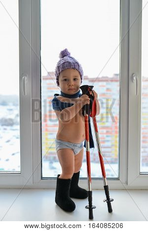 Cute little baby boy weared in winter clothes playing with trekking sticks standing near the window, high city buildings at background.