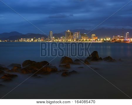 Nha Trang city skyline slow exposure over the bay just after sunset with the city lights ablaze.