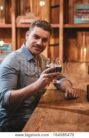 Great evening. Positive handsome good looking man sitting at the table and raising a glass with beer while enjoying his evening