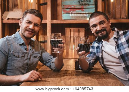 Relax after work. Pleasant joyful nice men sitting together at the table and drinking beer while resting after work in the pub