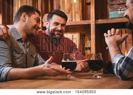 My best friend. Positive pleasant bearded man sitting next to his friend and hugging him while resting in the pub