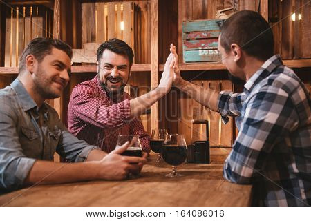 Positive emotions. Handsome cheerful male friends sitting opposite each other at the table and giving high five while being in the pub