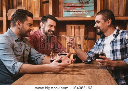 Involved in the discussion. Cheerful positive nice men having beer and interacting with each other while sitting at the table in the pub
