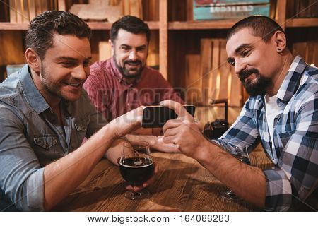 What is this. Pleasant nice cheerful man looking at the smartphone and pointing at its screen while sitting with his friends at the table