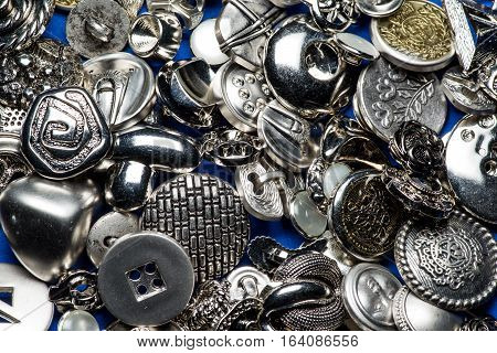 Collection of metallic sewing buttons on blue background