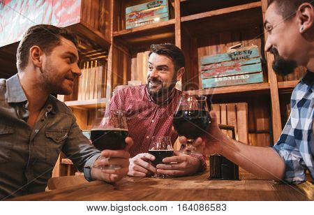 Evening in the pub. Cheerful nice pleasant men sitting around the table and chatting while resting together in the pub