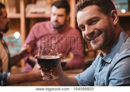 Cheers for you. Handsome happy delighted man raising his glass with beer and smiling while drinking for you
