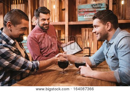 Pleasurable time. Handsome delighted nice friends shaking hands and smiling while sitting opposite each other at the table