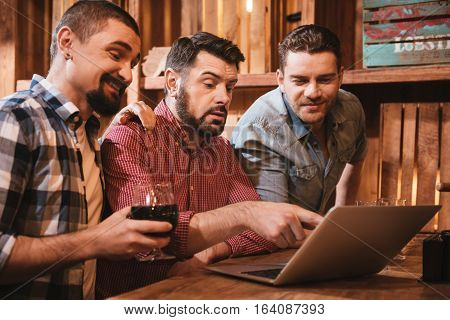 Look at this. Good looking cheerful pleasant man sitting at the laptop and pointing at the screen while showing something to his friends