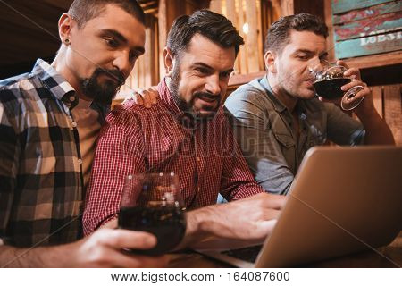 Being involved. Nice bearded handsome man sitting at the laptop and pressing a button on the keyboard while being with his friends in the pub