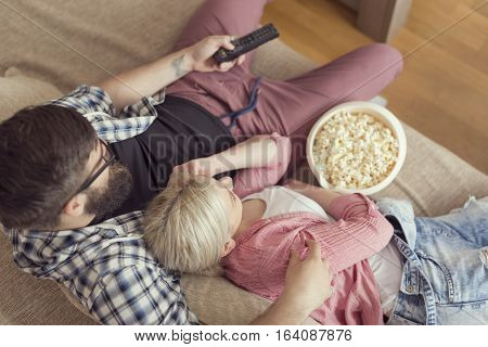 Top view of a couple enjoying their leisure time watching television and eating popcorn. Selective focus