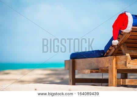 Santa Claus Hat on chair near tropical beach with turquoise sea water and white sand
