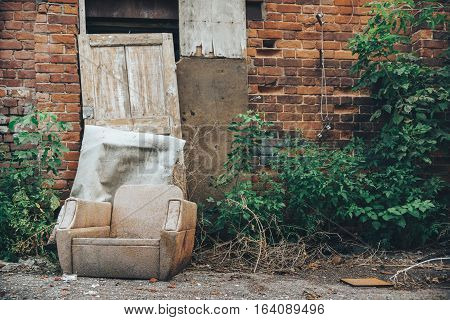 old chair on the brick wall background. cast housing. deserted place, abandoned by people