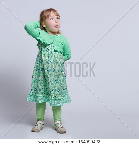 Cute little girl standing with hands behind her back and sticking out her tongue