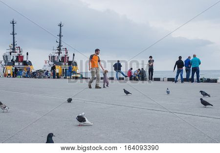 BATUMI GEORGIA - OCTOBER 9 2016: Unidentified people fishingresting and walking near the pier of Batumi.Batum is the second largest city of Georgia located on the coast of the Black Sea