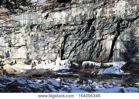 A rock face over a flowing creek with icicles and boulders.