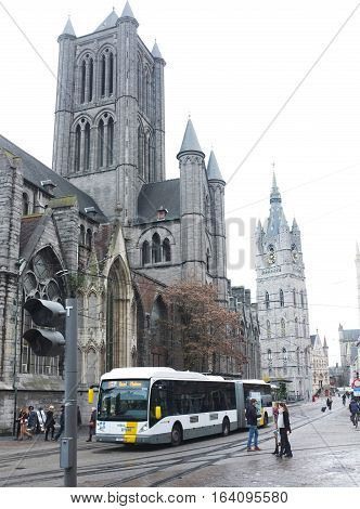 London, UK - November 17, 2016:  Public bus collects its passengers in front of Saint Nicholas' Church in the city centre of Ghent, Belgium