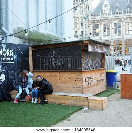 London, UK - November 19, 2016: Two teenage couples kiss each other next  to a closed little shop in the city centre of Ghent, Belgium