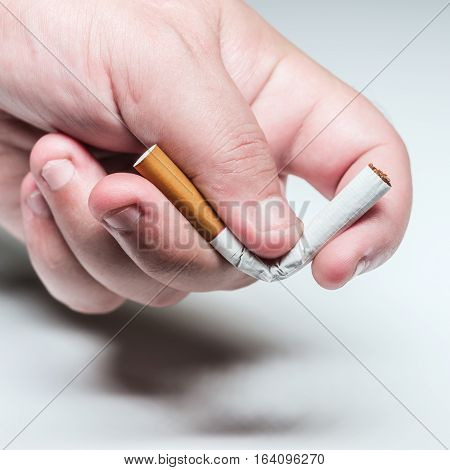Quit smoking conceptual image male hand bending a cigarette