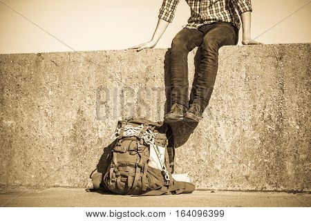 Man Tourist Backpacker Sitting On Grunge Wall Outdoor