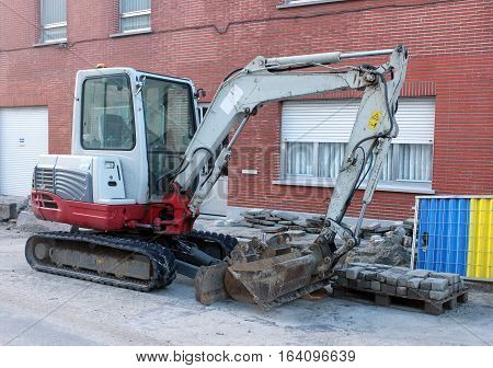Small excavator machine moving stones on the road