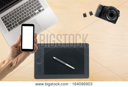 Male hand holding a smartphone with a blank screen over organized desk with laptop blurred in background with camera
