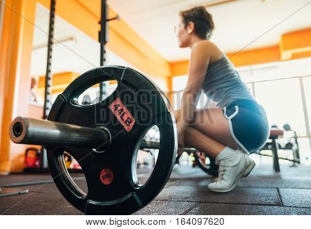 Girl at the gym doing exercise is the deadlift. Sitting near the top of the bar preparing to rise. Sports and active lifestyle. girl in blur.
